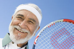 Happy Senior Tennis Player Holding Racquet. Close-up portrait of a happy senior male tennis player holding racquet against sky Royalty Free Stock Photography
