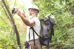 Happy senior tourist photographing himself in woodland Royalty Free Stock Image