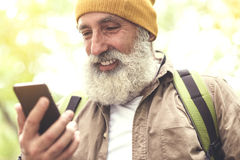 Happy senior tourist using phone for finding location Stock Photography