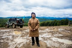 Happy senior tourist woman travel by jeep in mountain forest. In autumn with dramatic sky on background Royalty Free Stock Photography