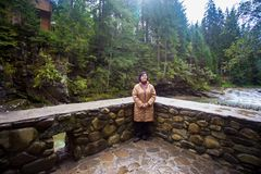 Happy senior tourist woman travel in mountain forest. In autumn with dramatic sky on background Stock Photos