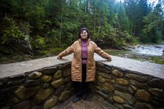Happy senior tourist woman travel in mountain forest. In autumn with dramatic sky on background Stock Image