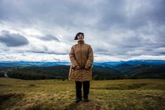 Happy senior tourist woman travel in mountain forest. In autumn with dramatic sky on background Stock Photography