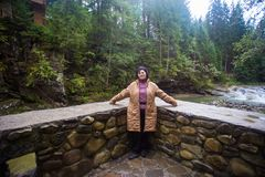 Happy senior tourist woman travel in mountain forest. In autumn with dramatic sky on background Royalty Free Stock Photos