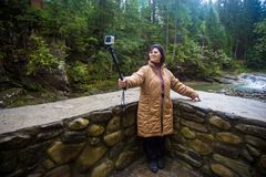 Happy senior tourist woman travel and takes selfie on action camera in forest mountain. In autumn day Royalty Free Stock Photo