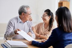 Senior couple having consultation. Happy senior Vietnamese couple in office of financial analyst Stock Photography