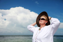 Happy senior woman. A smiling senior woman in a sun hat and sunglasses stock images