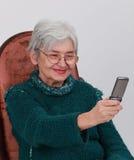 Happy senior woman. Portrait of a happy senior woman taking photos with a mobile phone Stock Photos