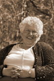 Happy senior woman. Senior woman sitting down for a portrait. She is happy stock photography