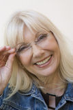 Happy Senior Woman Adjusting Glasses Stock Images