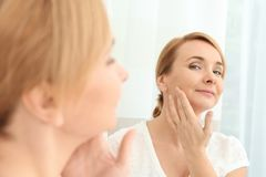 Happy senior woman applying anti-aging cream. Near mirror royalty free stock photography