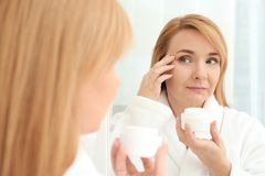Happy senior woman applying anti-aging cream. Near mirror royalty free stock photo