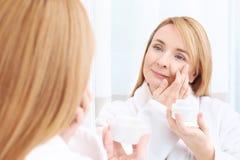 Happy senior woman applying anti-aging cream. Near mirror Stock Image