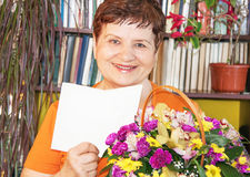 Happy senior woman with basket of flowers Stock Image