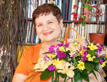 Happy senior woman with basket of flowers. Stock Photos