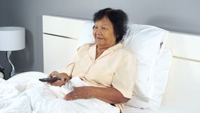 Senior woman in bed with remote control and watching tv. Happy senior woman in bed with remote control and watching tv stock video footage
