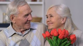Happy senior woman with bunch of flowers embracing husband, everlasting love. Stock footage stock video footage