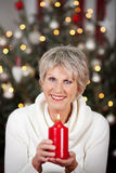 Happy senior woman with a burning candle Royalty Free Stock Photos