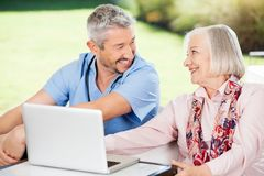 Happy Senior Woman And Caretaker With Laptop On. Happy senior women and caretaker looking at each other while using laptop on nursing home porch stock photos