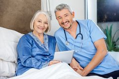 Happy Senior Woman And Caretaker With Tablet PC Stock Photos