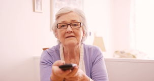 Happy senior woman changing channel with remote control stock video