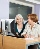 Happy Senior Woman With Classmate Using Computer In Class Stock Image