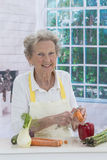 Happy senior woman cooking in kitchen royalty free stock photography