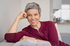 Happy senior woman on couch royalty free stock photos