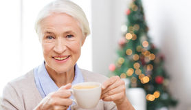 Happy senior woman with cup of coffee at home Stock Photo
