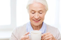 Happy senior woman with cup of tea or coffee Stock Photography