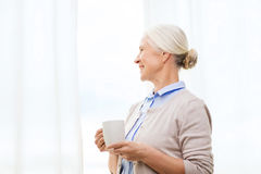 Happy senior woman with cup of tea or coffee Royalty Free Stock Photography