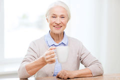 Happy senior woman with cup of tea or coffee Royalty Free Stock Image