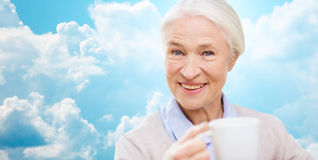 Happy senior woman with cup of tea or coffee Royalty Free Stock Images