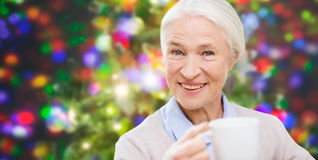 Happy senior woman with cup of tea or coffee Stock Photos