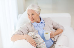 Happy senior woman with cup of tea at home Stock Image