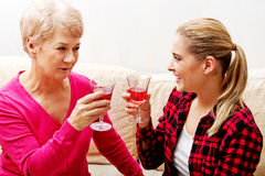 Happy senior woman with daughter or grandaughter drinking wine Royalty Free Stock Images