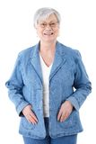 Happy senior woman in denim jacket smiling. Happy senior woman standing over white background, wearing denim jacket, smiling Royalty Free Stock Photos
