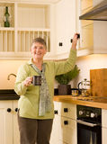 Happy senior woman in designer kitchen Royalty Free Stock Images