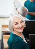 Happy Senior Woman At Desk In Computer Class Royalty Free Stock Photography