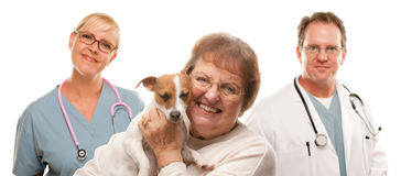 Happy Senior Woman with Dog and Veterinarian Team. Happy Senior Woman with Dog and Veterinarian and Nurse Isolated on a White Background Stock Images