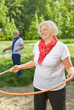 Happy senior woman doing sports with hoop Stock Image