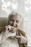 Happy senior woman eating biscuits Royalty Free Stock Image