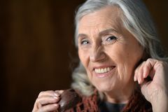 Happy senior woman eating chocolate cookie at home royalty free stock photo