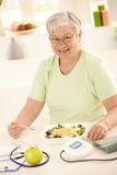 Happy senior woman eating salad. Happy senior woman eating healthy salad at home. Looking at camera, smiling Royalty Free Stock Photo