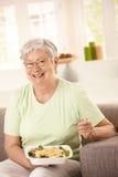 Happy senior woman eating salad. Happy senior woman eating healthy salad at home. Looking at camera, smiling Stock Image
