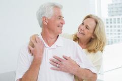 Happy senior woman embracing man from behind Stock Images