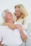 Happy senior woman embracing man from behind Stock Image