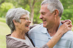 Happy senior woman embracing man at the park Royalty Free Stock Image