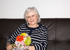 Happy senior woman enjoing her life. A woman showing that she enjoys retirement by relaxing and holding flowers Stock Images