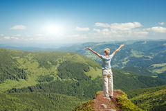 Happy senior woman enjoying the nature in the mountains. And looking on sky with raised hands. Freedom concept royalty free stock images